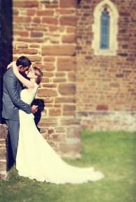 wedding-bride-and-groom-kissing-church-wall